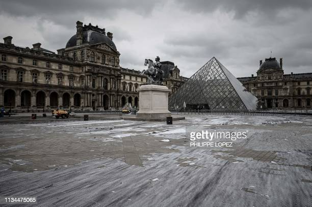 The remains of the installation of French contemporary artist and photographer Jean Rene aka JR are seen during cleaning works in front of the Louvre...