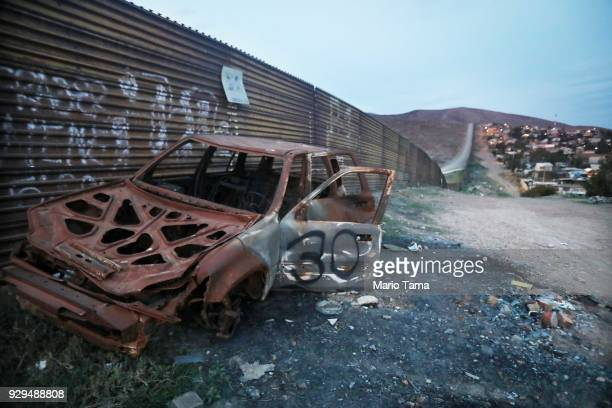 The remnants of a car sit on the Mexico side of the current US/Mexico border wall near to where President Donald Trump's border wall prototypes are...