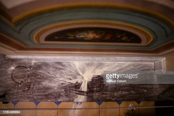 The remnants of pepper spray, tear gas, and fire extinguishers dusts the area around the northern entrance to the U.S. Capitol building on January 7,...