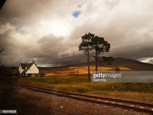 The remote railway station at Corrour in the west of Scotland with isolated trees under a heavy cloudy sky. Window reflections show that this shot is...