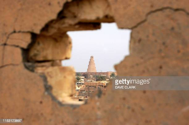 The renowned spiral minaret of the Great Mosque built by Caliph alMutawakil in the Iraqi city of Samarra in 847 AD appears through a hole punched...