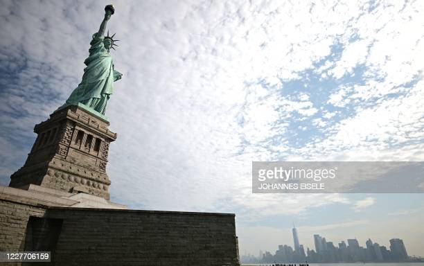 The reopened Liberty Island with the Statue of Liberty is pictured in front of the skyline of Lower Manhattan on July 20, 2020 in New York City. -...