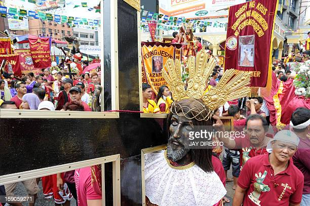 The replica of the religious icon the Black Nazarene is seen during a procession in Manila on January 7 2013 Filipino pilgrims began arriving in the...