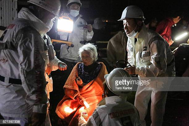 The rescue workers take care of an elderly woman suffering from the shock after the 73 magnitude earthquake at the evacuation center at the Mashiki...
