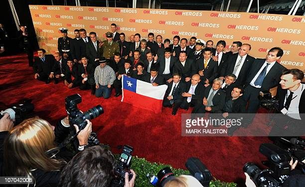 The rescued Chilean miners and their rescuers pose with their national flag on the red carpet of the 'CNN Heroes An AllStar Tribute' awards show at...