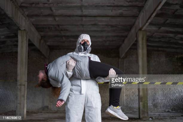 the rescuer carries the injured person in his arms. - doomsday clock imagens e fotografias de stock