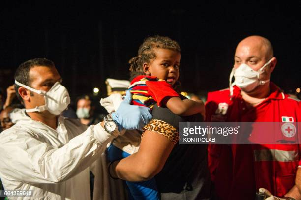 PORT CROTONE CALABRIA ITALY The rescuers help a eritrean child to disembark from the Italian Guard Coast ship with around 90 immigrants between men...