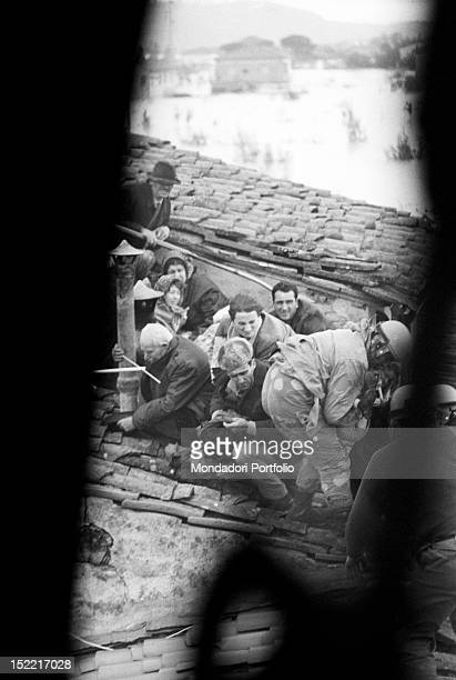 The rescuers reach some people who found refuge on the roof of their house during the flood Florence 1966