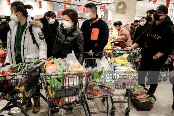 The resident wear masks to buy vegetables in the market on January 23th Hubei£¬China on January 23 2020 in Wuhan China Flights trains and public...