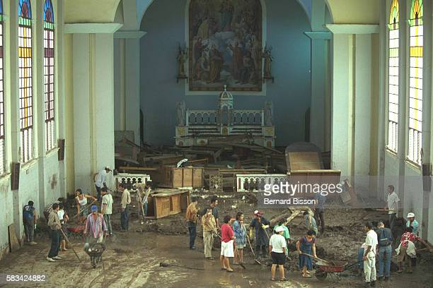 The residents get together to clean the Auxilia dora church that is full of mud