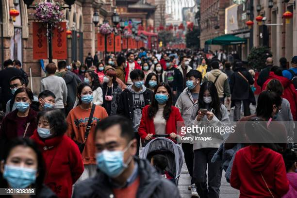 The residents wears the mask while walks in business street during the second day of the Spring Festival on February 13, 2021 in Wuhan, Hubei...