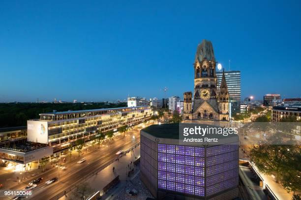 The restored Kaiser Wilhelm Memorial Church, also called the Gedaechtniskirche and the Bikini Berlin shopping center stand illuminated during blue...