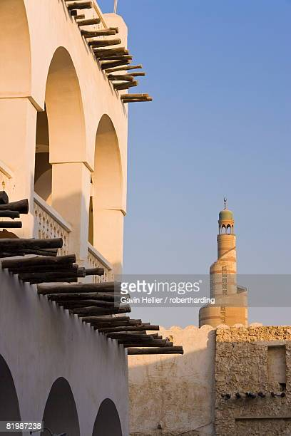 the restored souq waqif with mud rendered shops and exposed timber beams and the spiral mosque of the kassem darwish fakhroo islamic centre based on the great mosque in samarra in iraq, doha, qatar, middle east