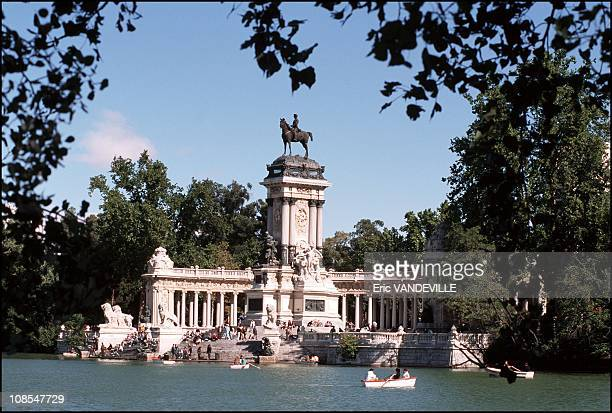 The Retiro gardens in Madrid. On the banks of the lake, where one may rent row boats stand the imposing monument to King Alfonso XII in Spain in...