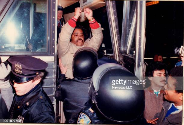 The Rev Al Sharpton raises his handcuffed hands as he boards a police bus after he was arrested at LaGuardia Airport in Queens New York on January 27...
