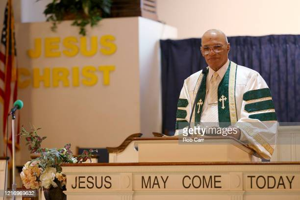 The Rev. Alvin Gwynn Sr. Stands at the lectern while hosting a walk thru Palm Sunday Service at Friendship Baptist Church held due to the COVID-19...