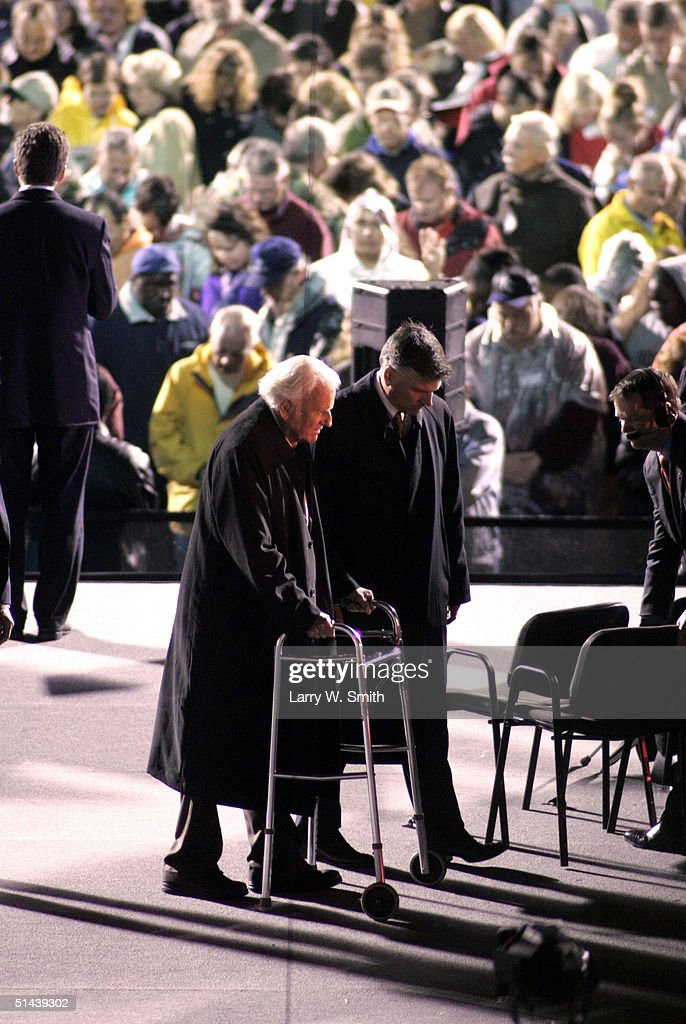 The Rev. Billy F. Graham (L) walks off the stage with the help of his son Franklin Graham before a crowd of thousands of people on a rainy night on October 7, 2004 at Arrowhead Stadium in Kansas City, Missouri. Graham is conducting his 'Heart of America' crusade in Kansas City October 7-10.