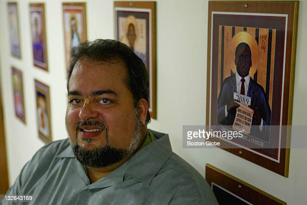 The Rev Dale Andrews poses in the hall of the Boston University School of Theology where a plaque of Martin Luther King hangs on the wall with other...