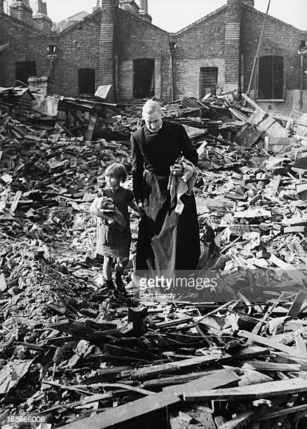 The Rev French the Church of England's Rural Dean of Stepney salvages clothes from a bombed house during the Blitz with the help of Helen Bush east...
