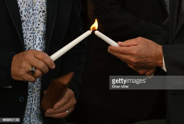The Rev Paul Goulet and the Rev David Shearin light candles during a prayer vigil outside Las Vegas City Hall in response to Sunday's mass shooting...