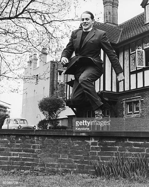 The Reverend David Sheppard leaps over a low wall at tHe Mayflower Family Centre in Canning Town 10th May 1962