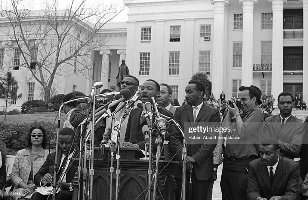 The Reverend Dr. Martin Luther King, Jr. (1929 - 1968) addresses supporters and fellow marchers outside the State Capital in Montgomery, Alabama at the end of the Selma to Montgomery march, late March 1965. His wife Coretta Scott (1927 - 2006) is visible on the far left, sitting next to the Rev. Ralph David Abernathy (1926 - 1990).