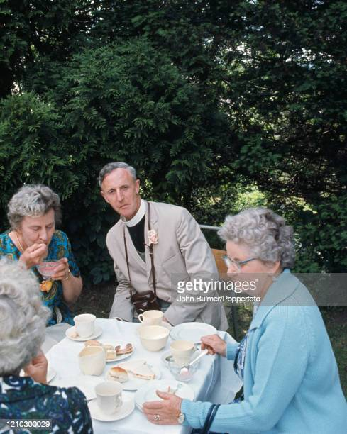 The Reverend Eric Andrews of the parish church of St Mary the Virgin with several of his parishioners enjoying afternoon tea at the church fete in...