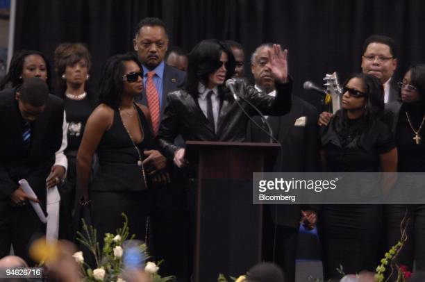 The Reverend Jesse Jackson red tie singer Michael Jackson waving and the Reverend Al Sharpton partially obscured behind Jackson's left hand give...