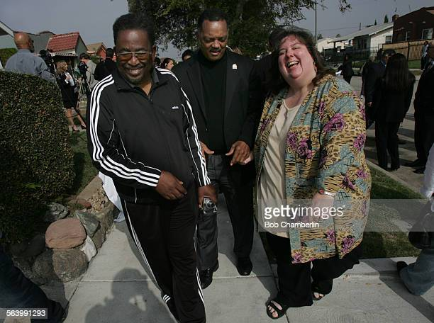 The reverend Jessie Jackson center shares a light moment as he takes a walk around the neighborhood with Ted Thomas left of the Park Mesa Heights...