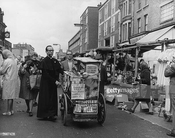The Reverend John Scott of Holy Trinity Church in Bow entertains the public in Roman Road Market East London with a barrel organ in order to raise...