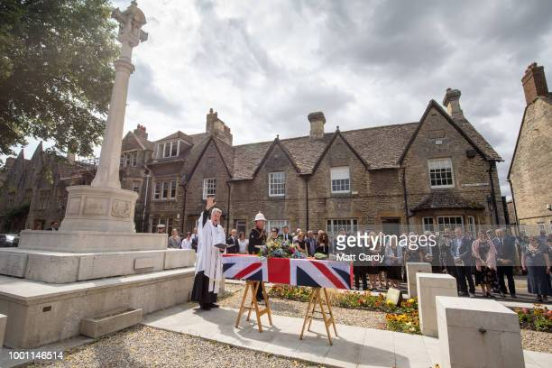 The Reverend Simon Kirby conducts a service besides the coffin of World War 2 veteran Patrick Churchill in front of the War Memorial on Church Green...