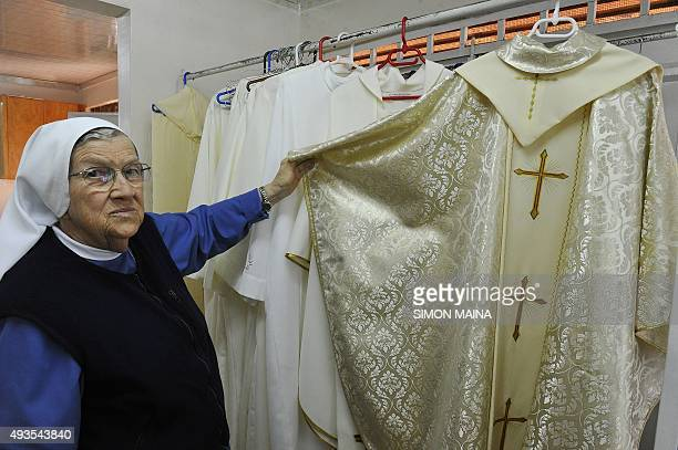 The Reverend Sister Ida Lagonegro shows the vestments Pope Francis will wear during his visit to the country in Nairobi on October 21 2015 The...