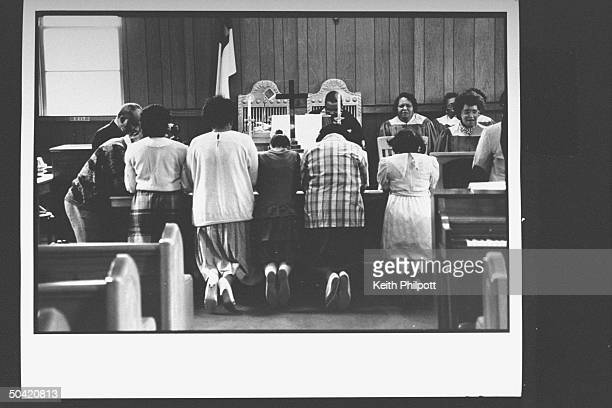 The Reverend Steven Jackson praying w his congregation at Model Chapel African Methodist Episcopal Church the sister church to his New Bethel Rocky...
