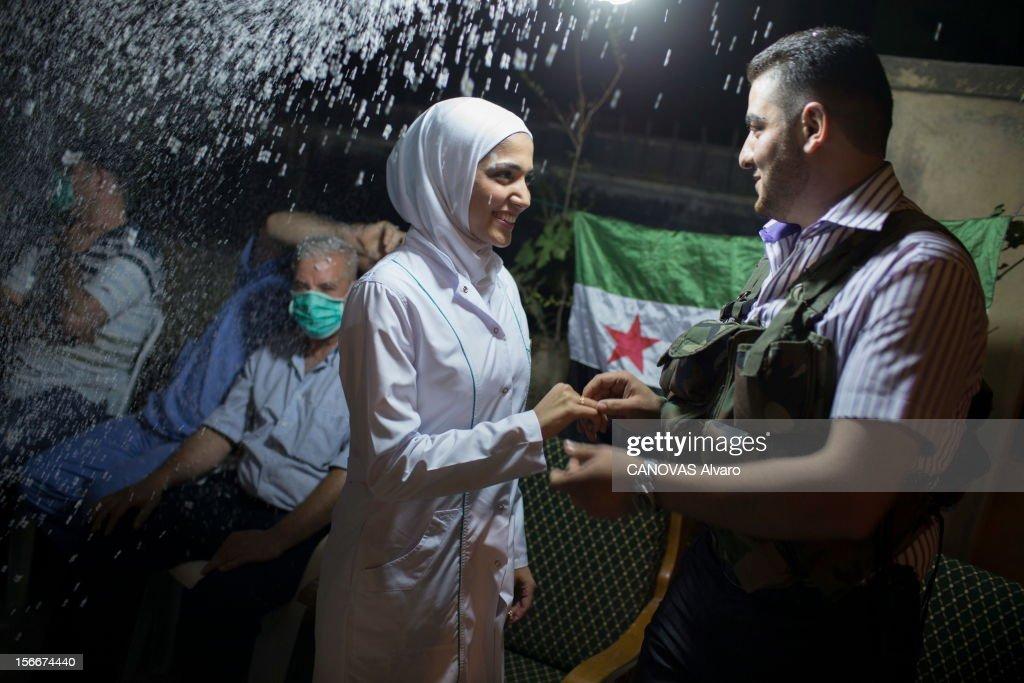 The Battle Aleppo. Révolte en Syrie contre le président Bachar El-Assad : la bataille d'Alep, août 2012. Les reporters de 'Paris Match' Alvaro Canovas et Alfred de Montesquiou ont rejoint les rebelles de l'Armée syrienne libre (ASL) qui défendent Alep, la capitale économique du pays, contre les forces pro-Assad de l'armée régulière et ses miliciens. jeudi 30 août, quartier de Salaheddine : ce soir, Hannan, une infirmière de 24 ans, épouse Hussein, 21 ans, sniper dans l'unité combattante (katiba) d'Abou Ali. Peu avant minuit, elle se marie avec pour toute robe sa blouse blanche et son voile de soignante. Au QG de l'unité de son mari, ils se disent 'oui' avec en guise de cotillons de la neige artificielle. Derrière la jeune mariée, un médecin du dispensaire dans lequel elle travaille veut rester anonyme par peur des représailles.