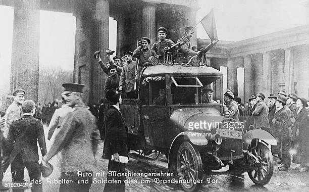 The Revolution in Berlin is shown with revolutionary soldiers with machine guns mounted on automobile roof passing through Brandenburg gate