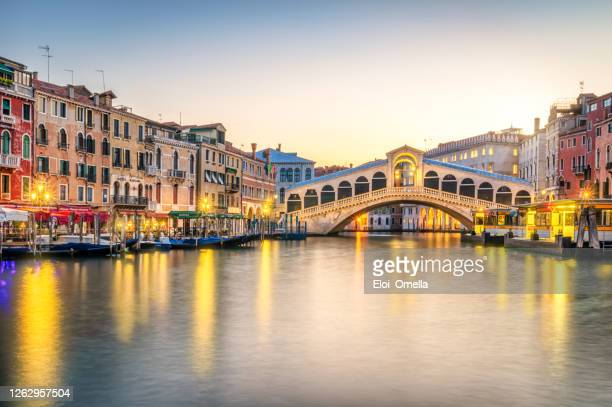 el puente de rialto y el gran canal de venecia, italia - venecia fotografías e imágenes de stock