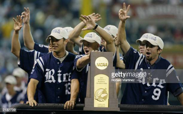 The Rice University Owls baseball team pose with the NCAA Division I Baseball Championship trophy before the MLB interleague game between the Texas...