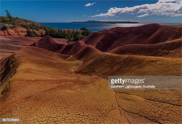 The rich red and ochre hues of the scarred landscape on Phillip island, situated just off Norfolk Island, south pacific ocean.