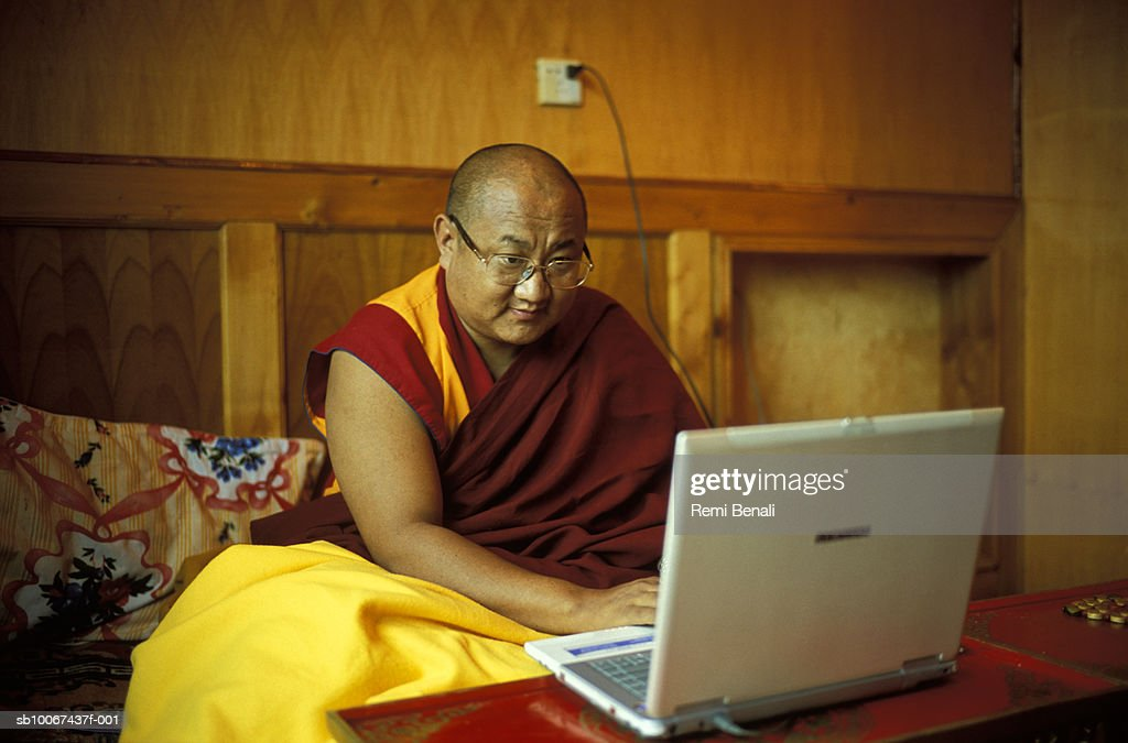 China, Sichuan Province, Litang, Rimpoche Xiaba monk using laptop in bedroom