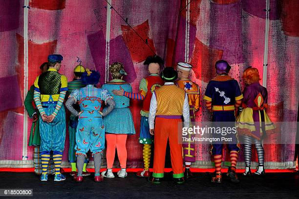The Ringling Bros clown troupe peek through the translucent curtain as they watch the final elephant show of their unit perform on the floor of the...
