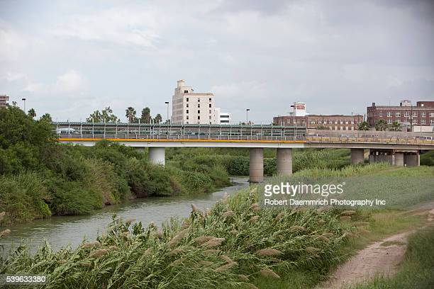 The Rio Grande River flowing through downtown Brownsville, looking west with Matamoros, Mexico on the left. The border wall is being built in...