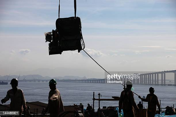 The Rio Niteroi bridge is seen in the background as workers lift a part for a Petroleo Brasileiro SA oil tanker under construction at the Maua SA...