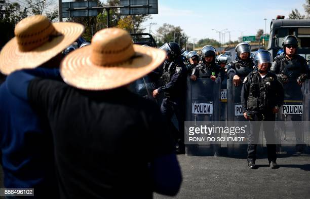 The riot police block Mexican farmers who are protesting in Mexico City on December 5 over land conflicts on the outskirts of the capital / AFP PHOTO...
