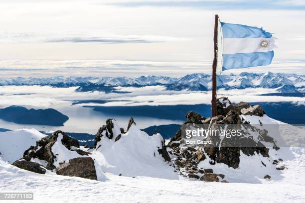 the ripped and torn argentina flag on the top of cerro catedral resort - リオネグロ州 ストックフォトと画像