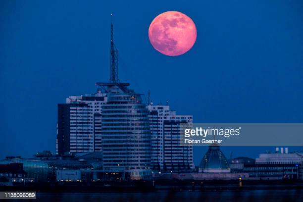 The rising full moon is pictured in front of the Bremerhaven cityscape with the Atlantic Sail City Hotel on April 19 2019 in Bremerhaven Germany