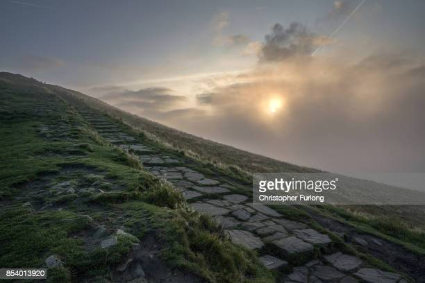 The rising sun burns off morning mist surrounding Mam Tor in the Hope Valley in the Peak District on September 26 2017 in Chapel en le Frith England
