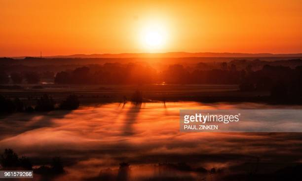 The rising sun burns off the morning fog near the village of Niederfinow in north eastern Germany on 23 May 2018 / Germany OUT