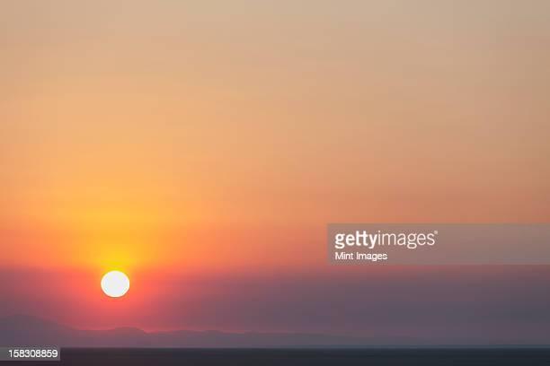 The rising sun over flat desert landscape at dawn in Nevada.