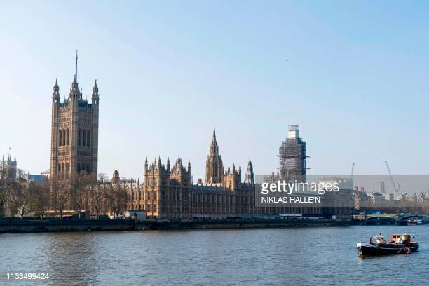 The River Thames and Houses of Parliament are pictured in the afternoon sunshine in central London on March 29 2019 British MPs on Friday rejected...