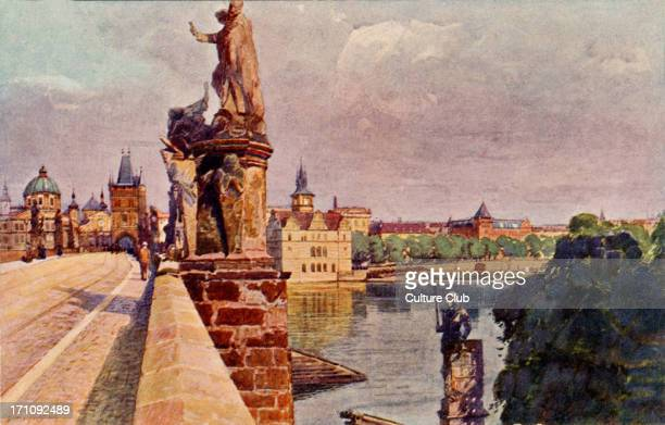 PRAGUE the river Vltava running under the Charles Bridge with its large statues and people walking along the side of the bridge Late 19thearly 29oth...